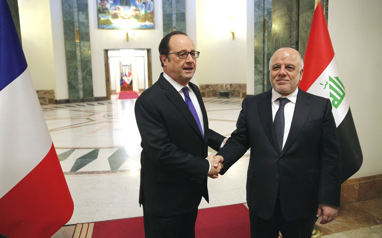 Iraq's Prime Minister Haider al-Abadi (R) greets French President Francois Hollande prior to their meeting in Baghdad on January 2, 2017. Hollande is in Iraq for a one-day visit to meet the French forces helping Iraq in the fight against the Islamic State group and to hold talks with top officials. / AFP PHOTO / POOL / Christophe Ena