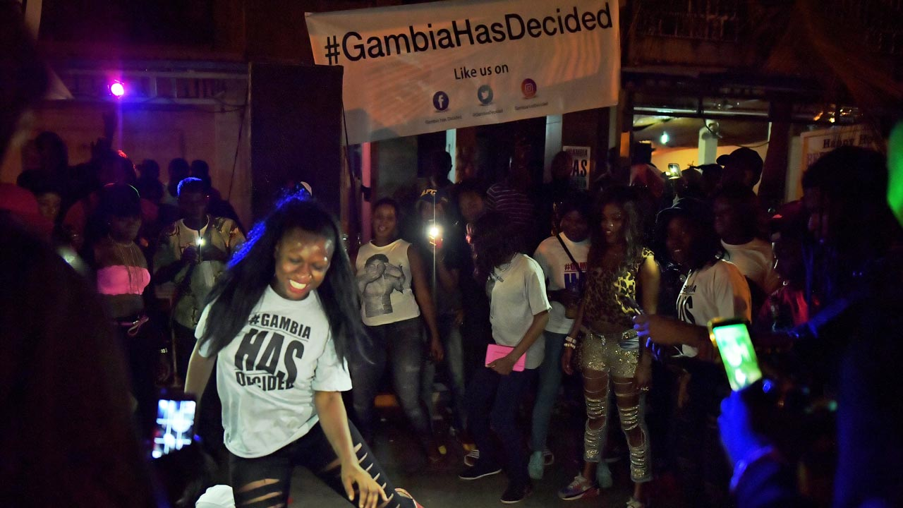 People dance in the streets after hearing of the confirmed departure of former Gambian leader Yahya Jammeh in Banjul on January 21, 2017. Yahya Jammeh, The Gambia's leader for 22 years, flew out of the country on January 21, 2017 after declaring he would step down and hand power to President Adama Barrow, ending a political crisis. An AFP journalist at the airport saw Jammeh board an unmarked plane heading for an unspecified destination, seen off by a delegation of dignitaries and soldiers. CARL DE SOUZA / AFP