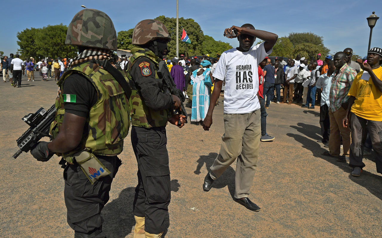 Soldiers of the Nigerian Special Boat Service (SBS) stand guard as people wait for the arrival of President Adama Barrow (not pictured) at the airport in Banjul on January 26, 2017. Jubilant Gambians on Janauary 26 welcomed home their new President Adama Barrow, who was elected almost two months ago but forced to flee to Senegal when his predecessor refused to step aside. Dressed in flowing white robes and cap, Barrow stepped off the plane, with heavily-armed troops from Senegal and Nigeria standing by as he flew in from Dakar where he had taken shelter on January 15./ AFP PHOTO / CARL DE SOUZA