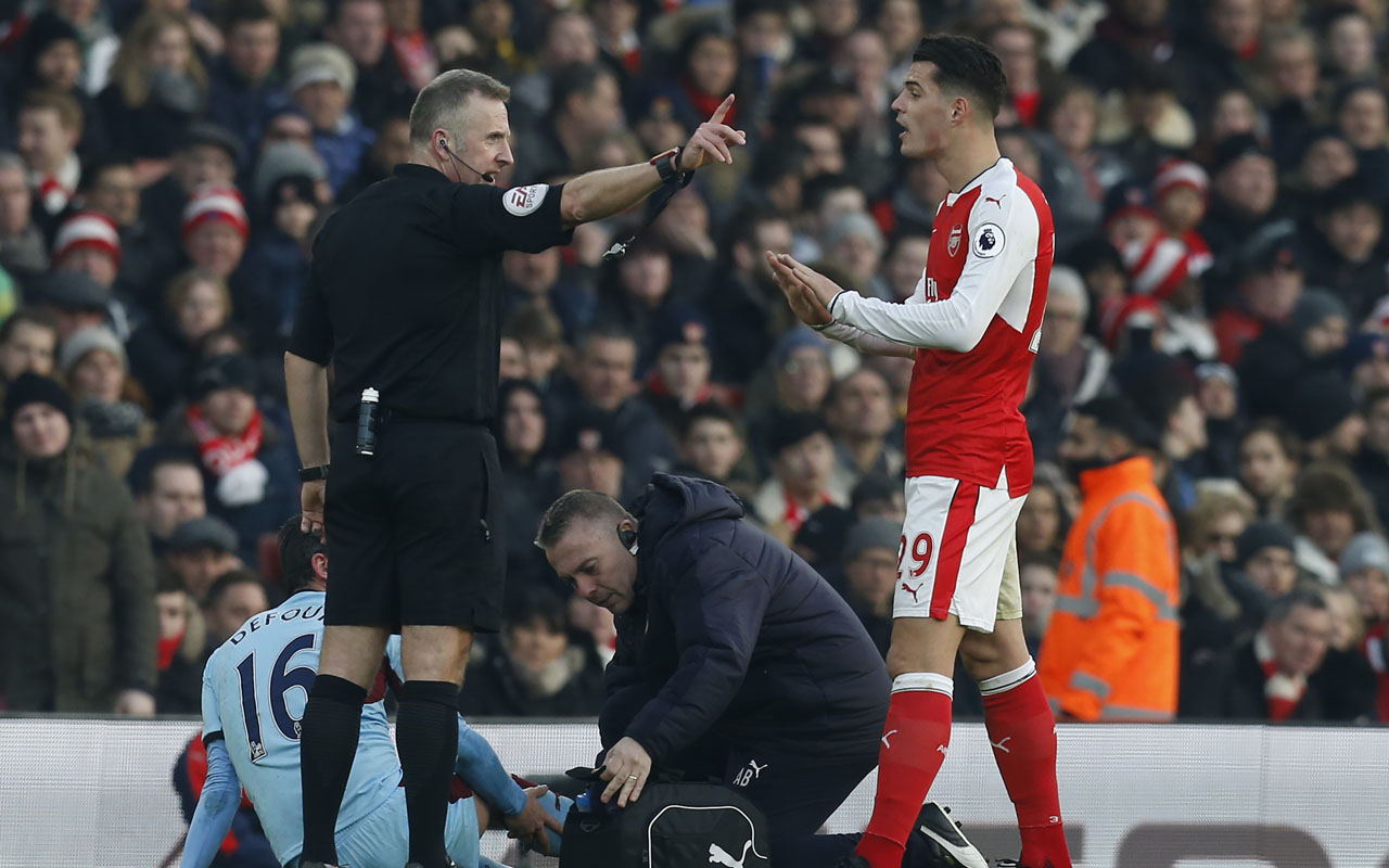 English referee Jonathan Moss (L) gestures to Arsenal's Swiss midfielder Granit Xhaka after he makes a challenge on Burnley's Belgian midfielder Steven Defour during the English Premier League football match between Arsenal and Burnley at the Emirates Stadium in London on January 22, 2017.  / AFP PHOTO / Ian KINGTON /