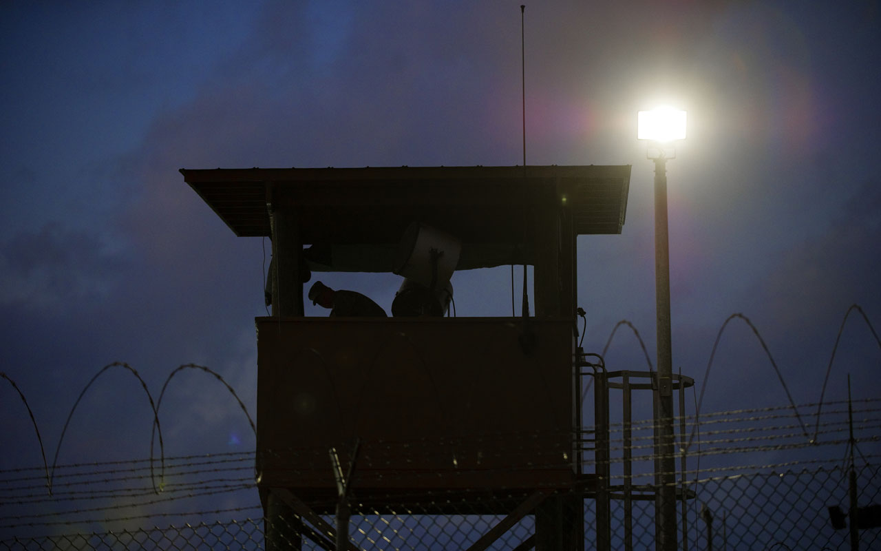 (FILES) In this March 30, 2010 file photo reviewed by US military officials, a member of the US military mans the guard post before sunrise at Camp Delta, part of the US Detention Center in Guantanamo Bay, Cuba. Despite a flurry of last-minute releases from Guantanamo Bay, President Barack Obama is set to fail in his eight-year quest to close the infamous military detention center. One of his first acts as president in 2009 was to issue an executive order to shut the controversial jail within a year, but it is clear it will remain open when he leaves office on January 20, 2017. / AFP PHOTO / PAUL J. RICHARDS