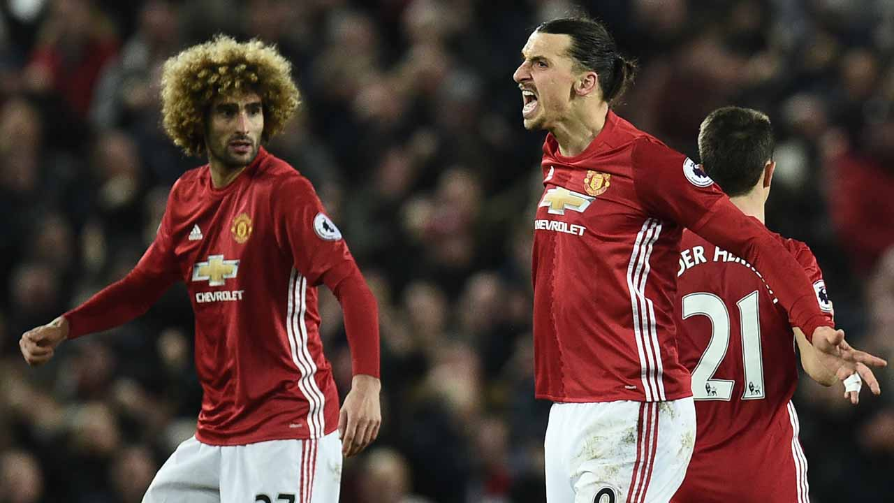 Manchester United's Swedish striker Zlatan Ibrahimovic (C) celebrates scoring his team's first goal with Manchester United's Belgian midfielder Marouane Fellaini (L) during the English Premier League football match between Manchester United and Liverpool at Old Trafford in Manchester, north west England, on January 15, 2017. The game finished 1-1. Oli SCARFF / AFP