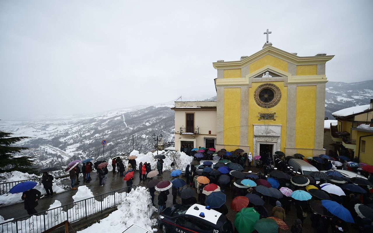 People gather at the church of San Nicola Vescovo on January 24, 2017 in Farindola for the funeral of Alessandro Giancaterino, one of the victims of the avalanche that hit the hotel Rigopiano after an earthquake on January 18, 2017 in central Italy. The death toll from the Hotel Rigopiano disaster climbed to 14 today when firefighters recovered the bodies of five more victims. As a result the number of people missing after an avalanche hit the Abruzzo mountain hotel last Wednesday has dropped to 15. / AFP PHOTO / FILIPPO MONTEFORTE