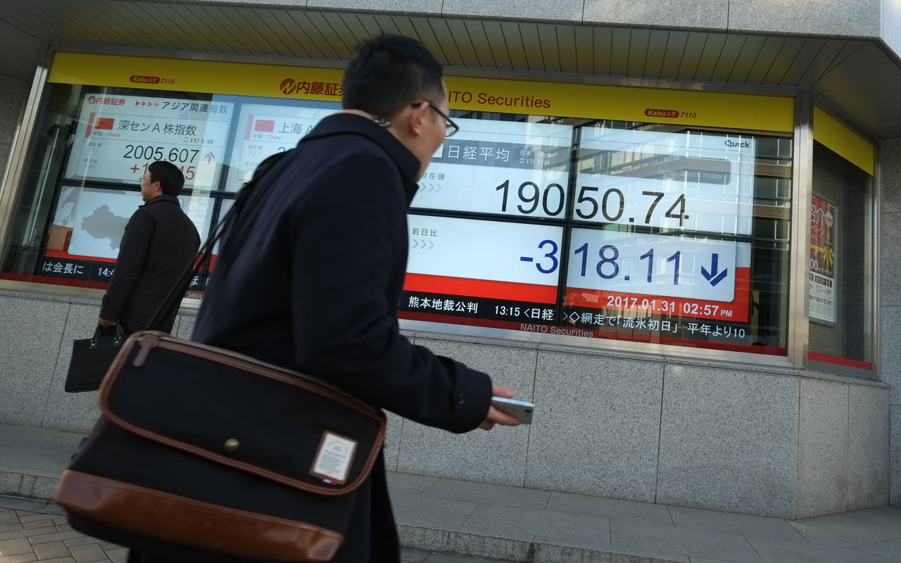 "A pedestrian walks in front of an electric quotation board flashing stock prices on the Nikkei key index of the Tokyo Stock Exchange in Tokyo on January 31, 2017. Japan's central bank hiked its economic growth forecasts on January 31, citing an improved global outlook and a weaker yen but the country's finance chief warned of ""uncertainty"" caused by the arrival of Donald Trump in the White House. / AFP PHOTO / Kazuhiro NOGI"