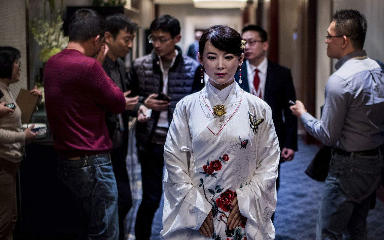 "Humanoid robot Jia Jia, created by a team of engineers from the University of Science and Technology of China, is seen following a presentation at a conference in Shanghai on January 9, 2017. ""Jia Jia"" can hold a simple conversation and make specific facial expressions when asked, and her creator believes the eerily life-like robot heralds a future of cyborg labour in China. Billed as China's first human-like robot, Jia Jia was first trotted out last year by a team of engineers at the University of Science and Technology of China. / AFP PHOTO / Johannes EISELE"