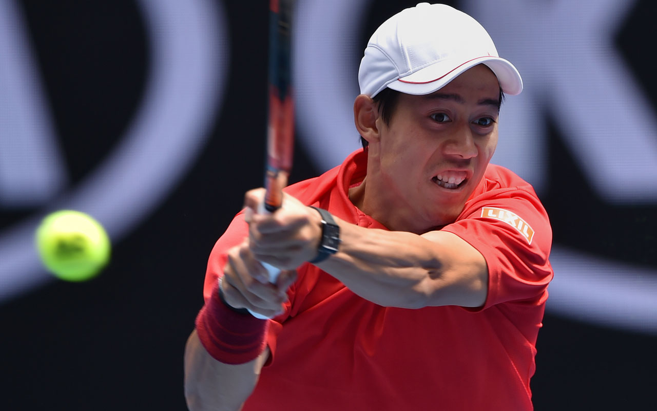 Kei Nishikori of Japan hits a return against Jeremy Chardy of France in their men's singles match on day three of the Australian Open tennis tournament in Melbourne on January 18, 2017. / AFP PHOTO / Peter PARKS /