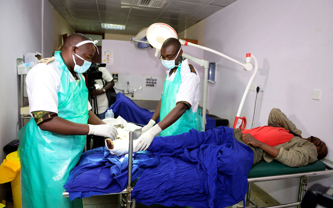 "(FILES) This file photo taken on December 10, 2016 shows Kenyan Defence force (KDF) doctors attending to an injured man at Kenyatta National Hospital in Nairobi. A Kenyan court has handed down a one-month suspended jail term to seven union officials over a doctors' strike which has crippled public hospitals for the last 40 days. However Judge Hellen Wasilwa said that if the doctors did not call off the strike within two weeks, the officials would ""be arrested and taken to jail."" / AFP PHOTO / JOHN MUCHUCHA"