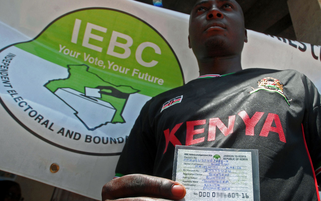 A potential voter holds his card after undergoing the voter registration process at the start of countrywide 14-day exercise at the Kenyan port city of Mombasa on January 16, 2017. Kenya's election commission on January 16 began a drive to register millions of new voters ahead of August elections, with rival parties going all out to get their supporters to sign up. Authorities estimate that some four to six million people have yet to register, crucial numbers that could swing the result. / AFP PHOTO / ANDREW KASUKU
