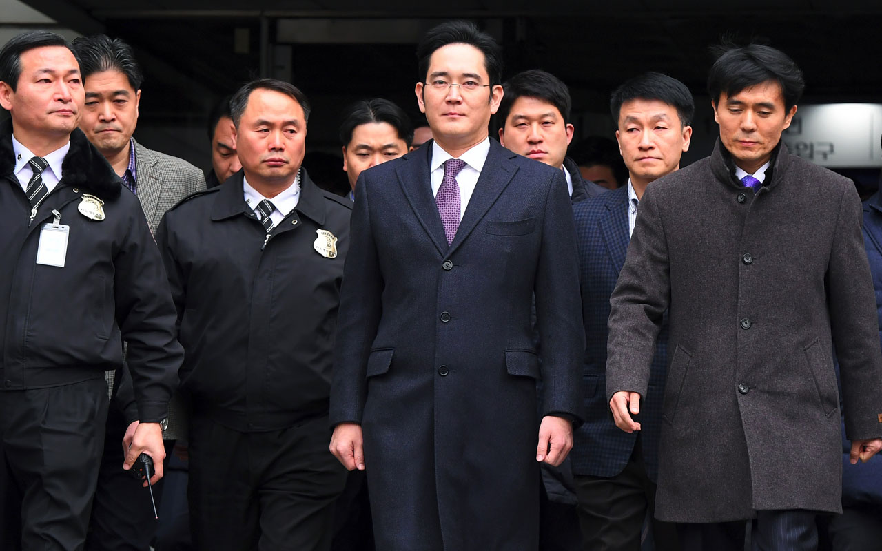 Samsung Group's heir-apparent Lee Jae-Yong (C) leaves for a waiting facility after attending a court hearing on whether he will be issued with an arrest warrant at the Seoul Central District Court in Seoul on January 18, 2017. The heir apparent to the Samsung business empire appeared at a South Korean court on January 18 as a judge began deliberating whether to formally arrest him over his alleged role in a snowballing corruption scandal engulfing President Park Geun-Hye. / AFP PHOTO / JUNG Yeon-Je