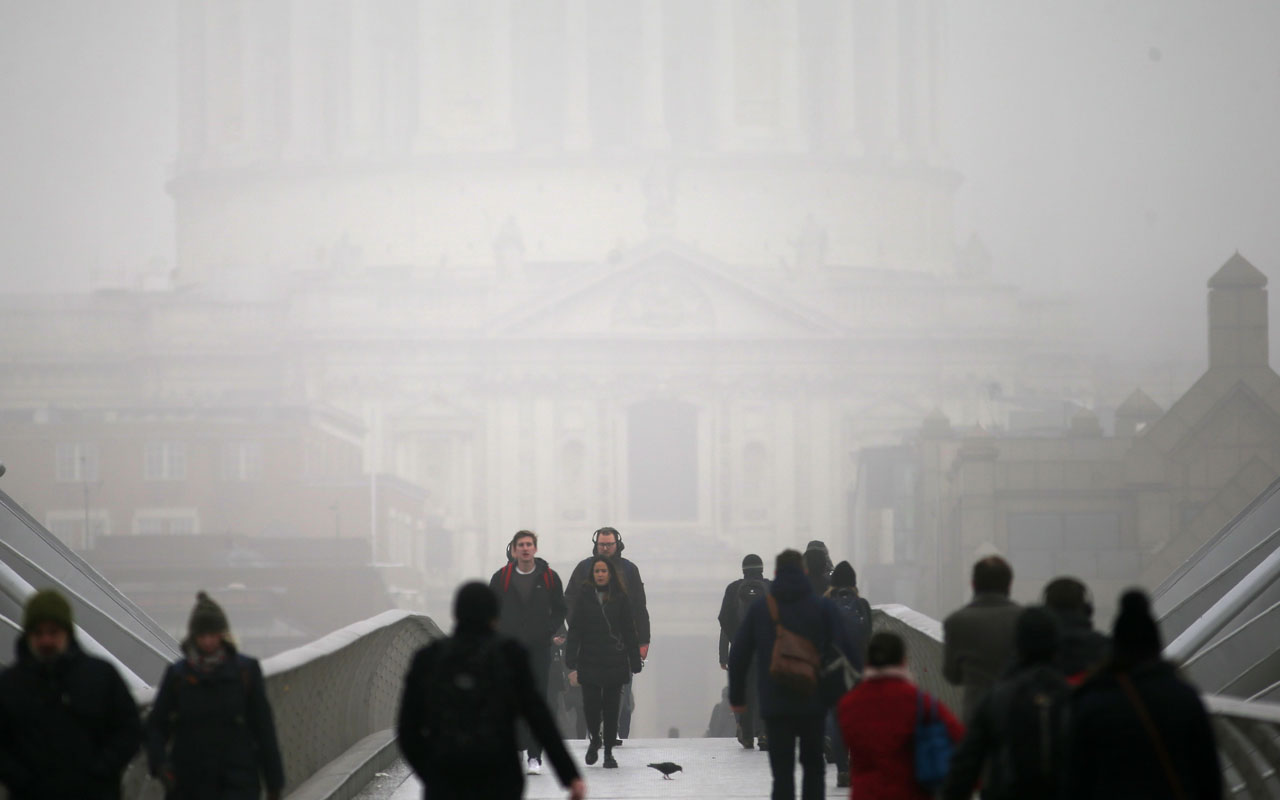 Pedestrians walk through fog as they cross the Millennium Bridge, backdropped by St Paul's Cathedral, in London on January 23, 2017. / AFP PHOTO / Daniel LEAL-OLIVAS