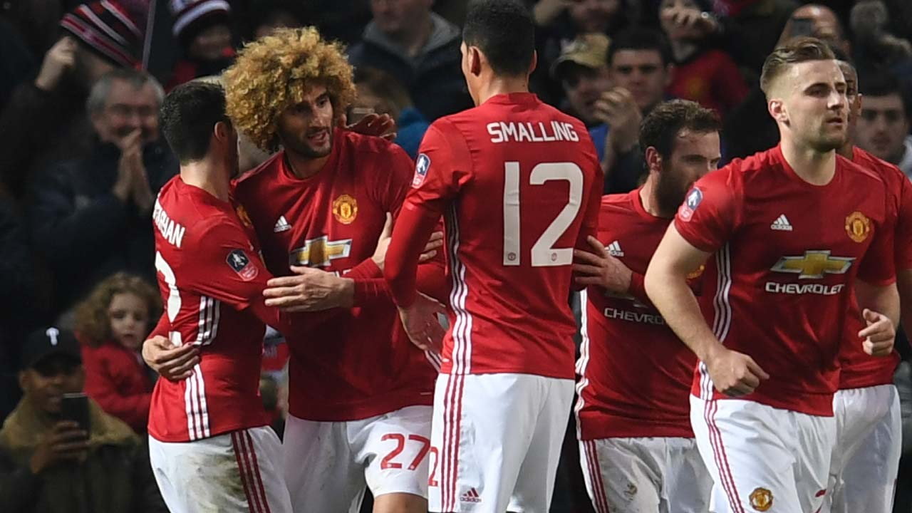 Manchester United's Belgian midfielder Marouane Fellaini (2L) celebrates with teammates after scoring his team's first goal during the English FA Cup fourth round football match between Manchester United and Wigan Athletic at Old Trafford in Manchester, north west England, on January 29, 2017. Paul ELLIS / AFP