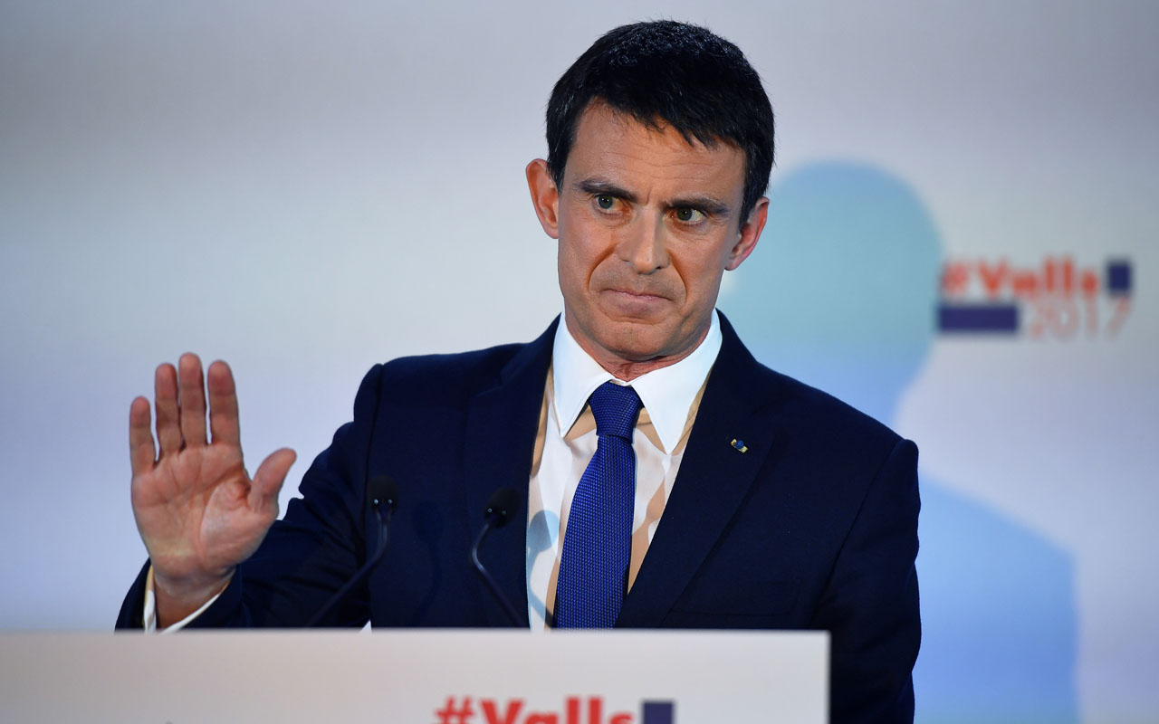 Former prime minister and candidate for the left-wing primaries, Manuel Valls gestures before speaking following the first round of the left-wing primary for the 2017 French presidential election, on January 22, 2017 at the Latin American House in Paris. Outsider Benoit Hamon came first in the French Socialists' presidential primary on January 22, 2017 and will stand against former prime minister Manuel Valls in a January 29 runoff, partial results showed. With just over one-third of polling stations reporting, Hamon scored 35.21 percent to 31.56 percent for Valls, with former economy minister Arnaud Montebourg eliminated along with four other candidates, party electoral official Thomas Clay announced. / AFP PHOTO / Eric FEFERBERG