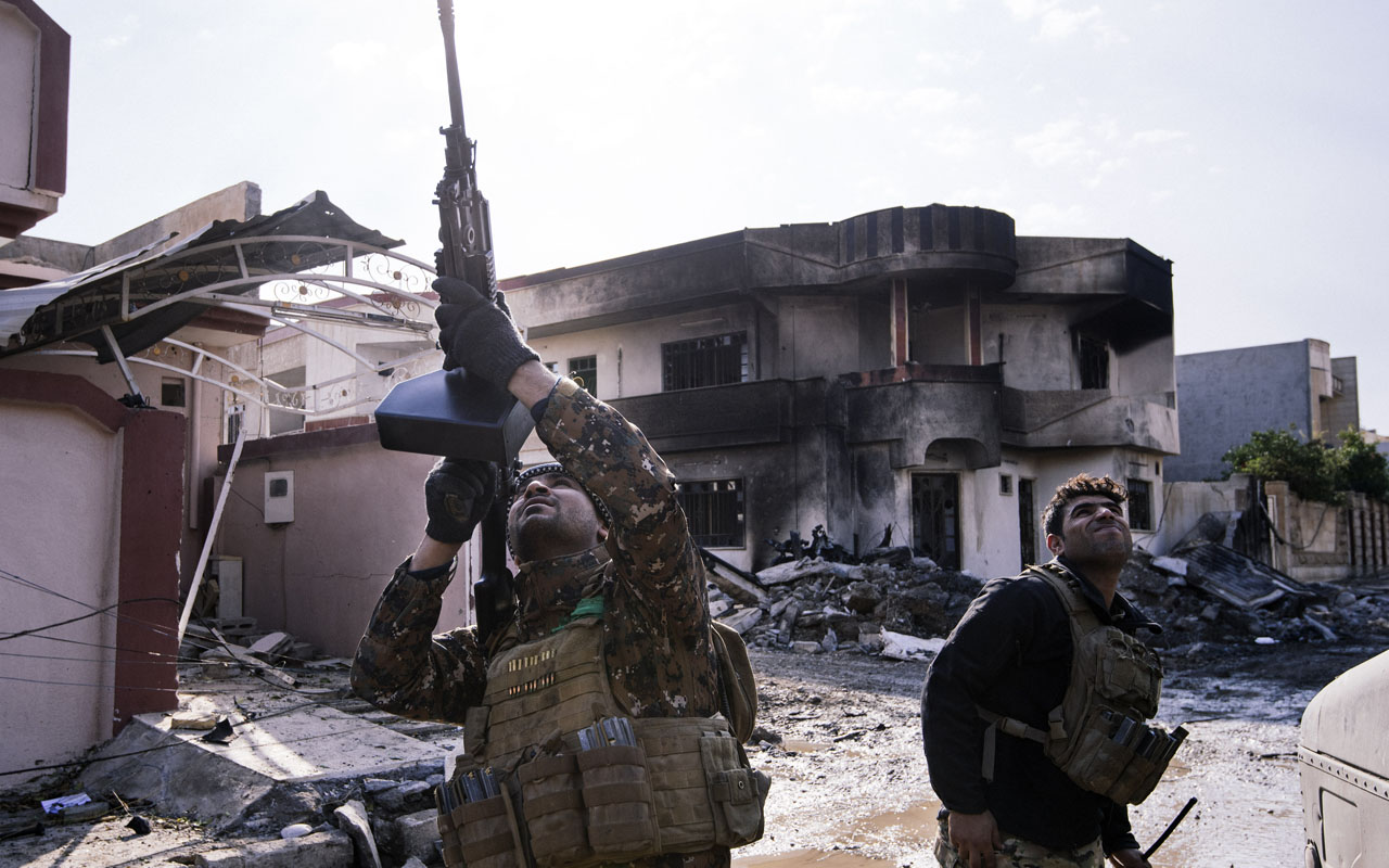An Iraqi special forces Counter Terrorism Service (CTS) member shoots at a drone flown by Islamic State group jihadists (IS) in Mosul's al-Rifaq neighbourhood on January 8, 2017, as an ongoing military operation against the militants continues. A relatively new threat in the war on the jihadists since they took over large parts of Iraq in 2014 comes from above, with the systematic use of cheap commercial drones by IS for reconnaissance purposes. / AFP PHOTO / Dimitar DILKOFF / TO GO WITH AFP STORY BY GUILLAUME DECAMME