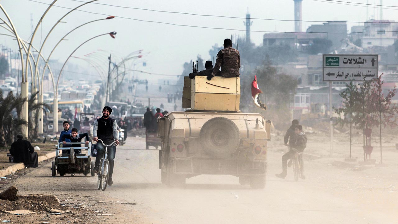 An man cycles past an Iraqi forces humvee driving on a street near the University of Mosul after its liberation from the Islamic state group (IS) control, during the ongoing military operation against the jihadists, on January 21, 2017. Iraqi forces battled the last holdout jihadists in east Mosul after commanders declared victory there and quickly set their sights on the city's west, where more tough fighting awaits. AHMAD AL-RUBAYE / AFP