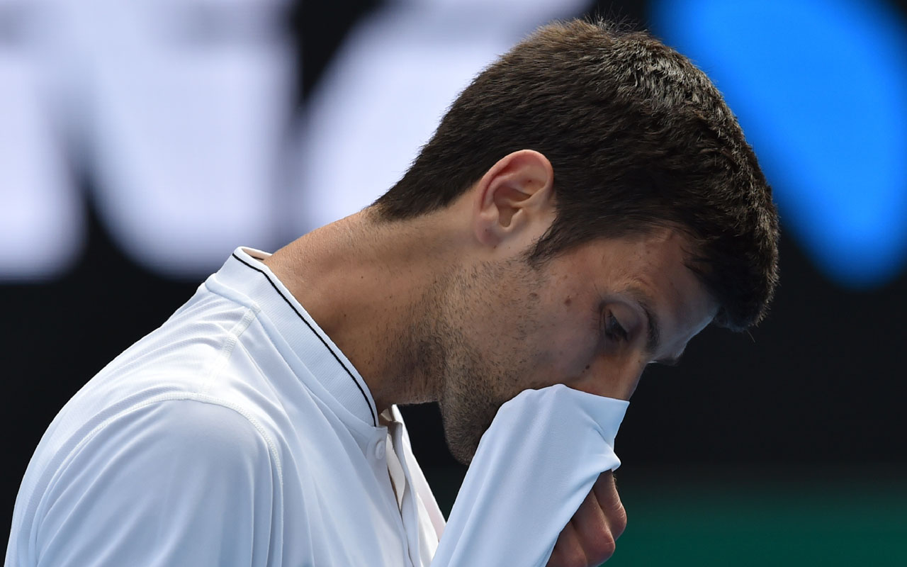 Serbia's Novak Djokovic reacts after a point against Uzbekistan's Denis Istomin during their men's singles match on day four of the Australian Open tennis tournament in Melbourne on January 19, 2017. / AFP PHOTO / PAUL CROCK /