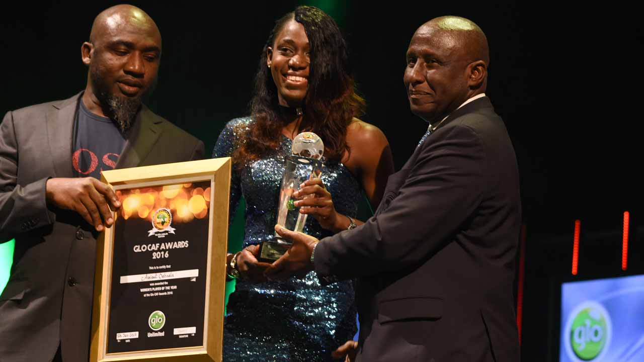 Woman Player of the Year Asisat Oshoala (C) receives her award during the African Footballer of the Year Awards in Abuja, on January 5, 2017. Algerian and Leicester striker Riyad Mahrez has been crowned the CAF African best Footballer for 2016 and beating former best player and Gabonese forward Pierre-Emerick Aubameyang and Sehegalese striker Sadio Mane, for the continent's most prestigious individual award. PIUS UTOMI EKPEI / AFP