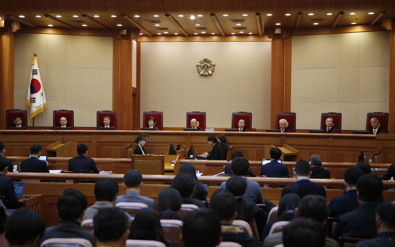 Nine judges of South Korea's Constitutional Court sit during the first hearing arguments for South Korea's President Park Geun-hye's impeachment trial at the Constitutional Court in Seoul on January 3, 2017. Parliament voted on December 9 to impeach Park over the scandal and her executive powers have been handed to an acting president, Prime Minister Hwang Kyo-Ahn. The impeachment case is being considered by the Constitutional Court, which has up to six months to reach a ruling. / AFP PHOTO / POOL / KIM HONG-JI