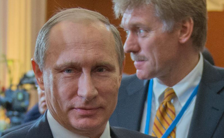 Kremlin spokesman Dmitry Peskov, seen in background with Russian President Vladimir Putin (AFP Photo/Sergei Guneev)