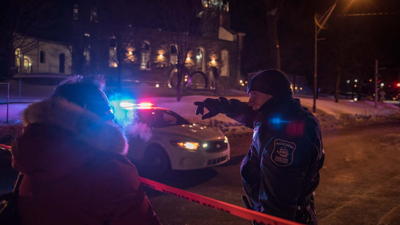 A Canadian police officer talks to a woman after a shooting in a mosque at the Québec City Islamic cultural center on Sainte-Foy Street in Quebec city on January 29, 2017. Two arrests have been made after five people were reportedly shot dead in an attack on a mosque in Québec City, Canada.  Alice Chiche / AFP
