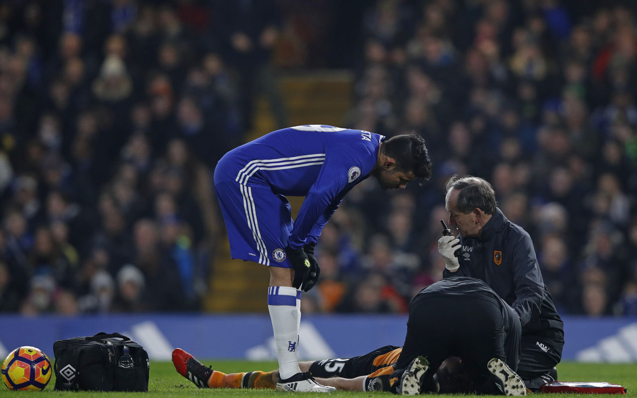 Hull City's English midfielder Ryan Mason receives medical treatment after a clash of heads as Chelsea's Brazilian-born Spanish striker Diego Costa shows his concern during the English Premier League football match between Chelsea and Hull City at Stamford Bridge in London on January 22, 2017. / AFP PHOTO / Adrian DENNIS /