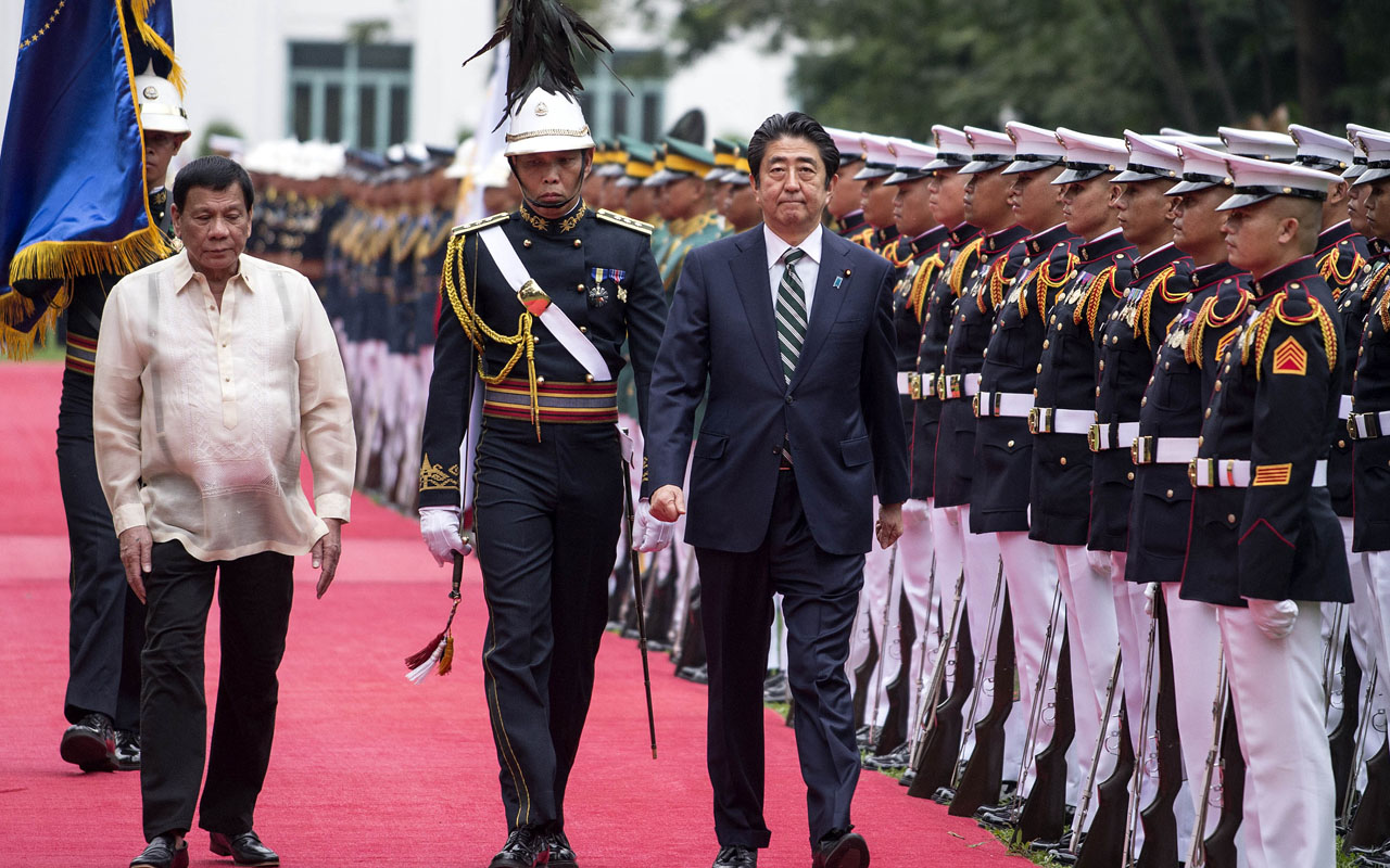 Philippine President Rodrigo Duterte (L) and Japanese Prime Minister Shinzo Abe (C) inspect an honour guard during a welcoming ceremony at the Malacanang Palace in Manila on January 12, 2017. Prime Minister Abe arrived in the Philippines on January 12, becoming the first foreign leader to visit since President Rodrigo Duterte took office last year and launched his deadly war on crime. / AFP PHOTO / NOEL CELIS