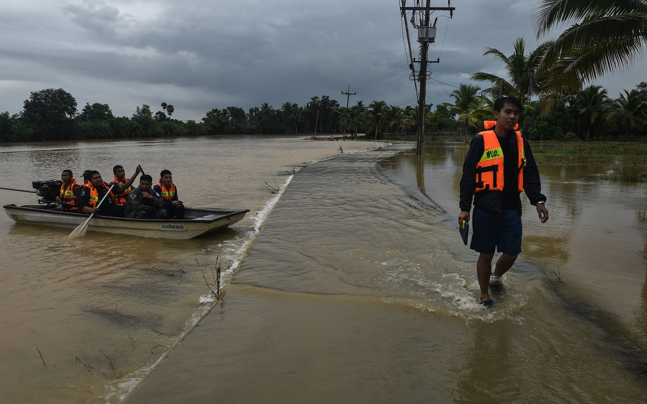 Thai soldiers in a boat approach a flooded village road in the Chaiya district of Thailand's southern province of Surat Thani on January 10, 2017. Overland routes to Thailand's flood-hit south were severed on January 10 after two bridges collapsed following days of torrential rain that has killed at least 25 people, including a five-year-old girl. / AFP PHOTO / LILLIAN SUWANRUMPHA