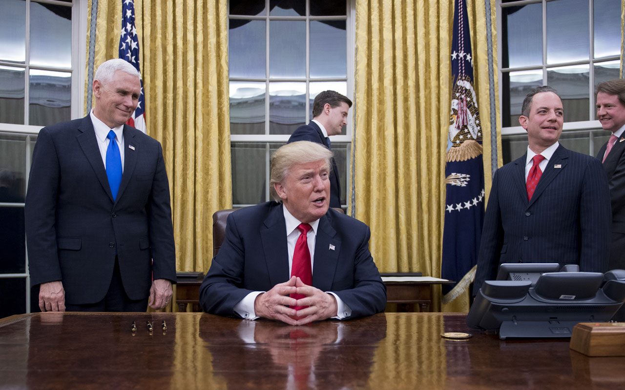 US President Donald Trump (C) speaks to the press as he waits at his desk before signing conformations for General James Mattis as US Secretary of Defense and General John Kelly as US Secretary of Homeland Security, as Vice President Mike Pence (L) and White House Chief of Staff Reince Priebus (R) look on, in the Oval Office of the White House in Washington, DC, January 20, 2017. / AFP PHOTO / JIM WATSON