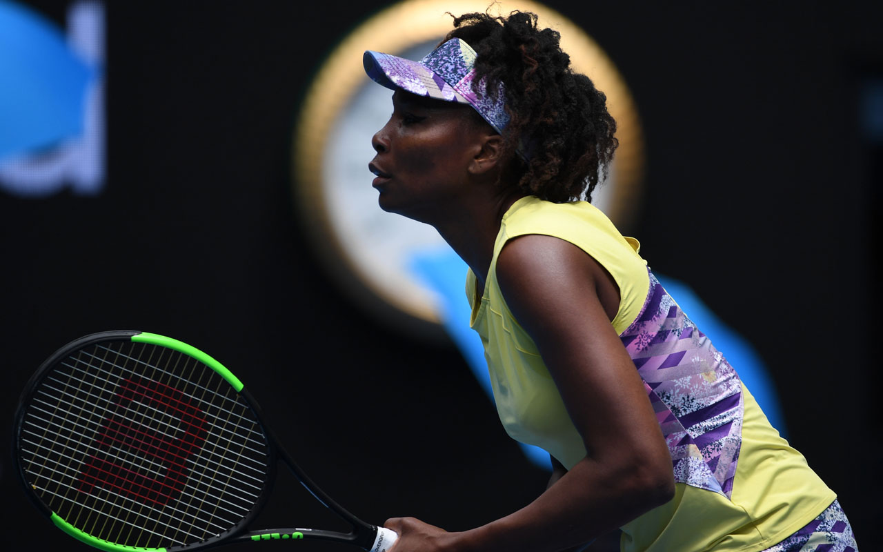 Venus Williams of the US prepares to return serve against Switzerland's Stefanie Voegele during their women's singles match on day three of the Australian Open tennis tournament in Melbourne on January 18, 2017. / AFP PHOTO / SAEED KHAN /