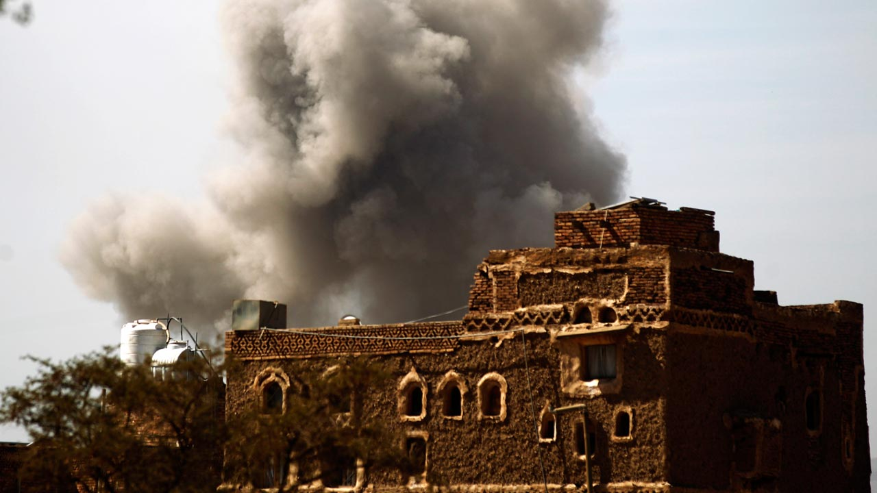 Smoke billows behind a building following a reported air strike by the Saudi-led coalition in the Yemeni capital Sanaa on January 22, 2017. MOHAMMED HUWAIS / AFP