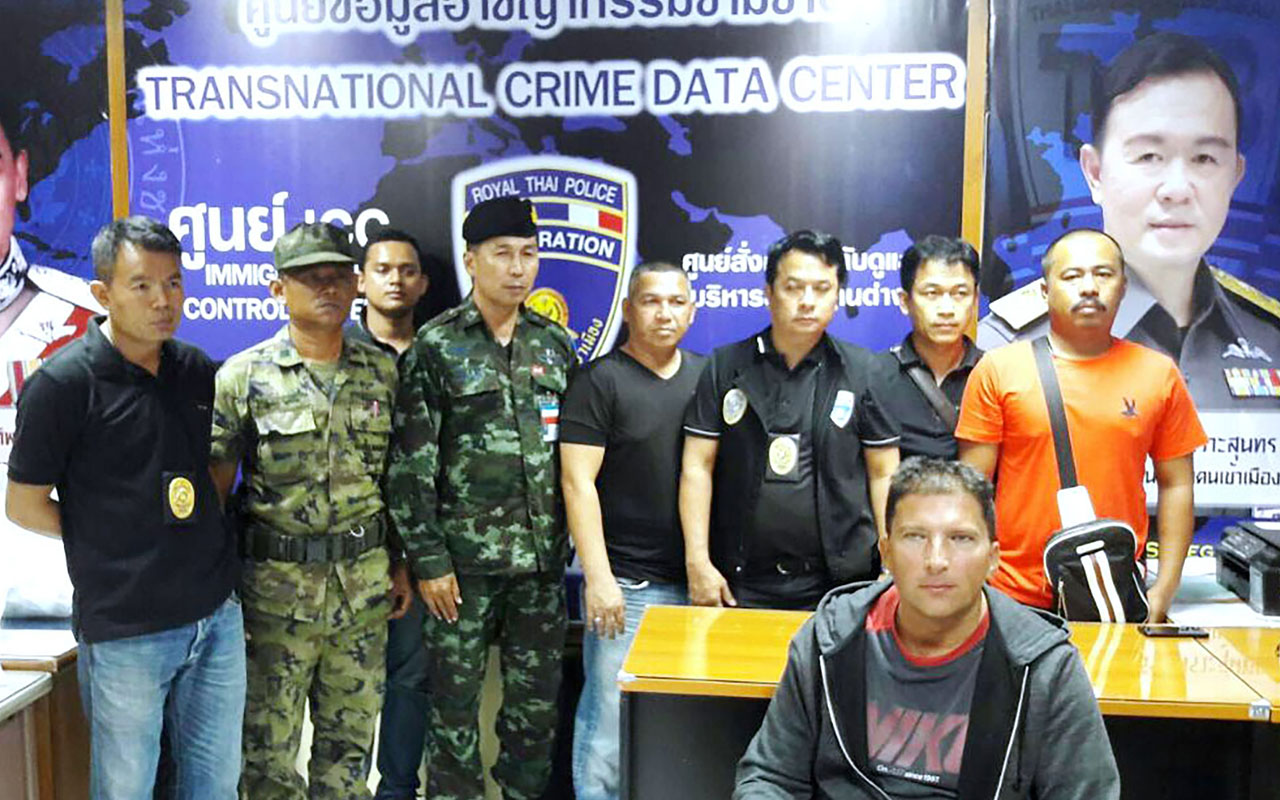 This handout photograph from the Royal Thai Police taken Jannuary 17, 2017 and released January 18, 2017 shows Zdenek Pfeifer (front R) sitting in front of Thai police after being detained on the island of Phuket. A Czech fugitive wanted in his homeland for knowingly spreading HIV to multiple victims has been arrested on a Thai resort island after living in the country for more than a year, police said January 18. / AFP PHOTO / Royal Thai Police / STR /