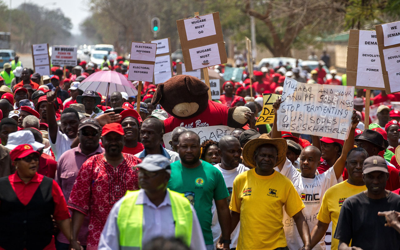 protesters holding placards as Zimbabwe opposition supporters under the National Electoral Reform (NERA) coalition march through the streets of Zimbabwe's second largest city Bulawayo to demand electoral reforms. For opponents of Zimbabwe's veteran President Robert Mugabe, internet data charges have become a key battlefront in their campaign against a regime that often cracks down violently on dissent. Last week, the state's telecommunications authority approved a sharp increase in mobile data prices -- triggering a furious public response that forced a surprise U-turn. Facebook, Twitter and WhatsApp activity was a driving force behind a new protest movement last year that led to work boycotts and street demonstrations that shook the regime of 92-year-old Mugabe. / AFP PHOTO / ZINYANGE AUNTONY