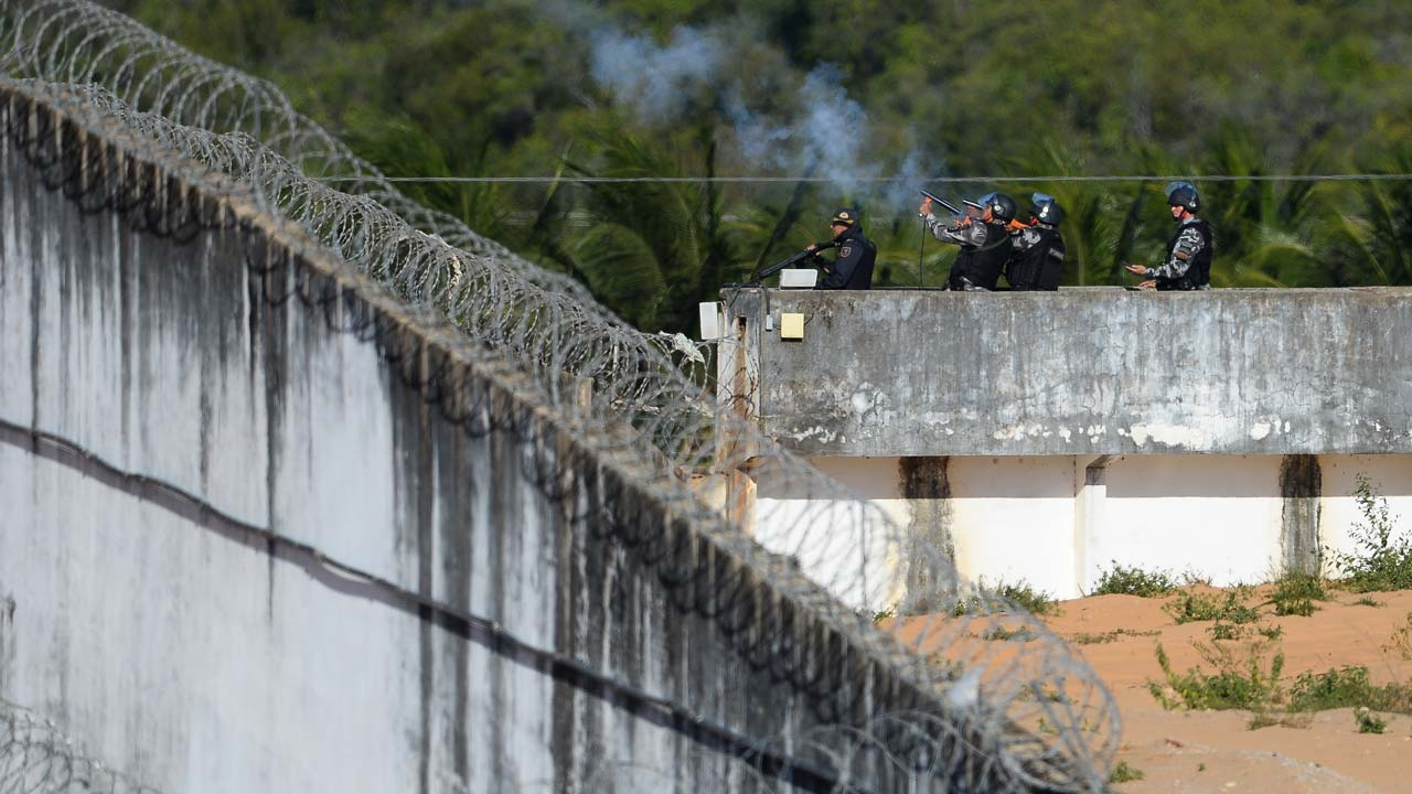 Police fire tear gas grenades at the inmates gathering on the roofs of the Alcacuz Penitentiary, near Natal, on January 19, 2017. Stick-wielding inmates hurled stones and lit fires Thursday in the jail where dozens were previously massacred, as authorities struggled to contain a spreading wave of gang violence. The governor of the surrounding Rio Grande do Norte state, Robinson Faria, called for the armed forces to deploy in the streets of Natal after rioting spread beyond the prison. ANDRESSA ANHOLETE / AFP