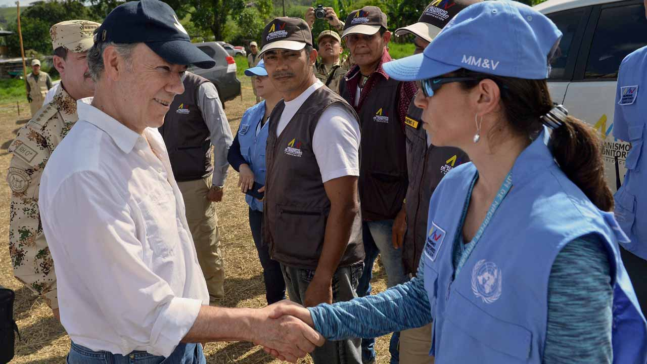 Handout picture released by the Colombian Presidency showing President Juan Manuel Santos greeting a UN representative who is part of the Tripartite Mechanism for Monitoring and Verifying the Cessation of Fire and Bilateral and Definitive Hostilities and Detachment of Weapons during his visit to one of the camps monitored and verified by the UN that will receive the members of the FARC guerrilla before laying down their arms after the peace agreement signed with the Colombian government in November that seeks to overcome half a century of armed conflict, in Mesetas, department of Meta, Colombia on January 5, 2017. The FARC's 5,700 fighters are currently gathering near 26 zones where they are due to demobilize over a period of six months in transition to be reintegrated into society. The UN has sent 280 monitors to oversee the process, a contingent set to eventually number 450. JUAN DAVID TENA / PRESIDENCIA DE COLOMBIA / AFP