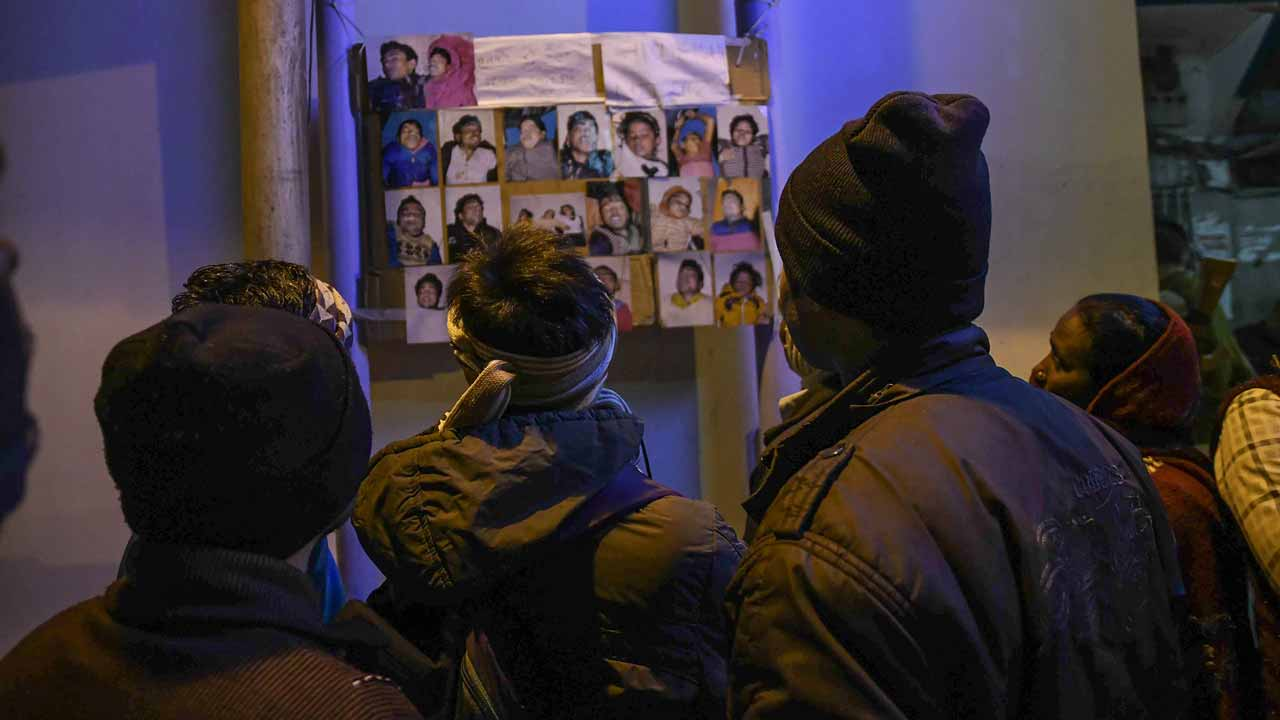 Relatives look at the images of people who drowned in a boat accident on the river Ganges near Patna in eastern India, on January 15, 2017. At least 19 people died January 14 after a boat carrying some 40 revellers returning from a kite festival capsized in the Ganges river in eastern India, police said. AFP