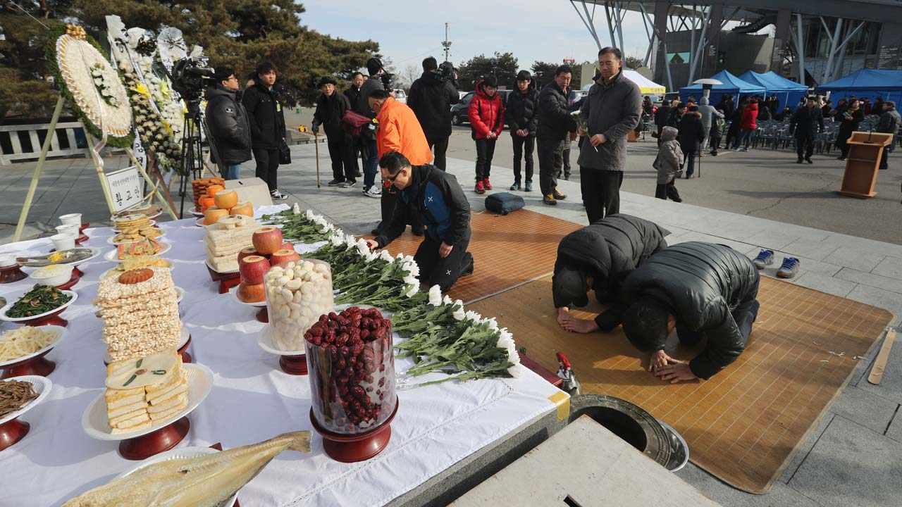 People bow to an altar at the Imjingak Peace Park in Paju, near the Demilitarized Zone (DMZ) separating North and South Korea, on January 28, 2017. On the frozen banks of the Imjin river, South Koreans divided from their families decades ago by war gathered to pay respects to their ancestors. Mostly elderly men -- according to tradition, Korean ceremonies for the lunar new year must be carried out by the eldest son -- they lined up before an altar piled with offerings of rice cakes, fruit and fish. STR / YONHAP / AFP