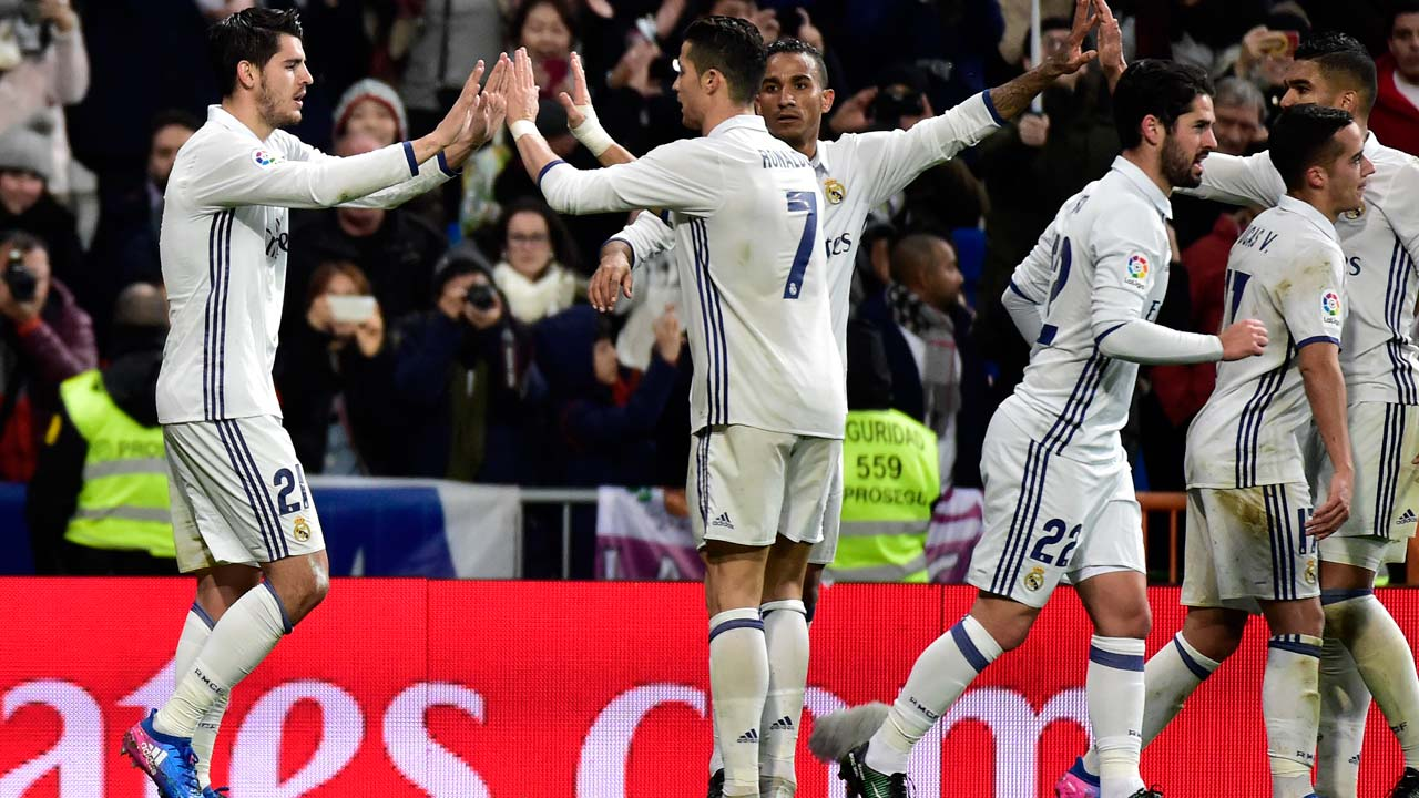 Real Madrid's forward Alvaro Morata is congratuled by Real Madrid's Portuguese forward Cristiano Ronaldo (2L) after scoring a goal during the Spanish league football match Real Madrid CF vs Real Sociedad at the Santiago Bernabeu stadium in Madrid on January 29, 2017. GERARD JULIEN / AFP