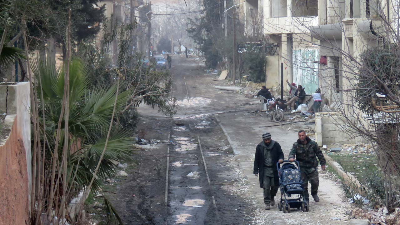 Syrians walk down an abandoned railway track in the town of Ain al-Fijeh in the Wadi Barada area on the northwestern outskirts of the Syrian capital on January 29, 2017. The Syrian army announced that it had recaptured the Wadi Barada area which had been the scene of fierce fighting in recent weeks between regime and rebel forces that tested a fragile nationwide truce and left millions in Damascus facing water shortages. STRINGER / AFP