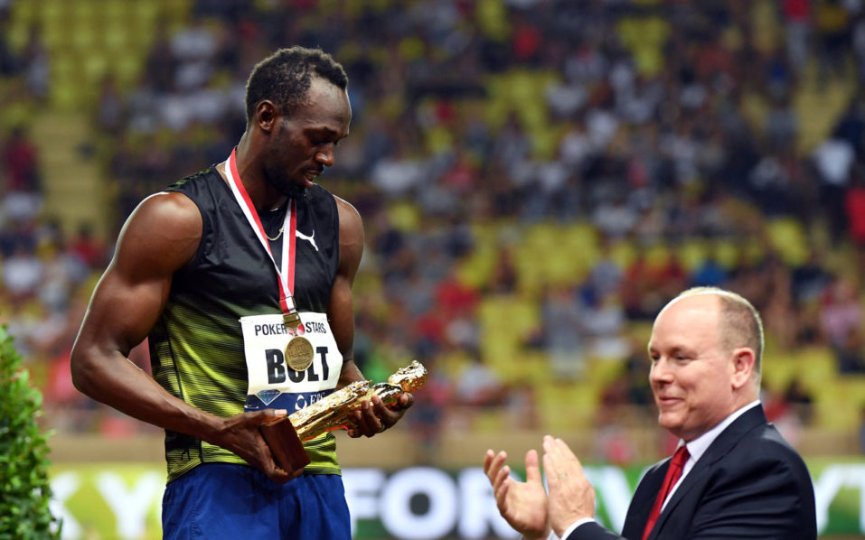 723924c0b18 Jamaica s Usain Bolt (L) looks at his trophy flanked by Prince Albert II of  Monaco (R) after winning the men s 100m event at the IAAF Diamond League ...