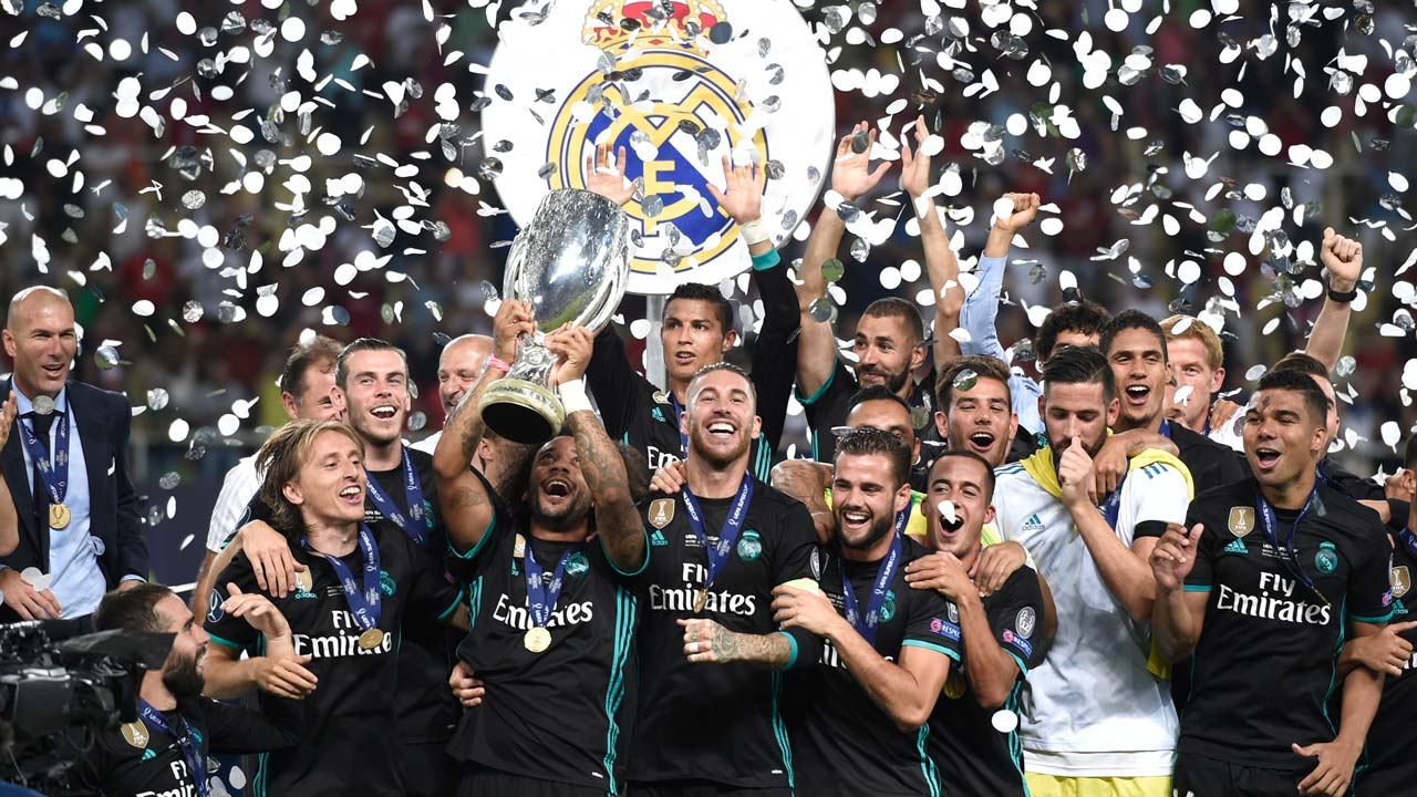 8cbd320aba1 Real Madrid s players celebrate with the trophy after winning the UEFA  Super Cup football match between Real Madrid and Manchester United on  August 8