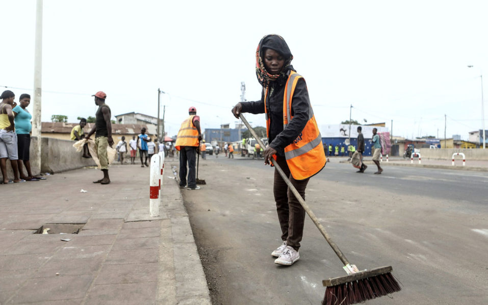 Workers clear a street following an anti-government protest in Lome on October 19, 2017. Protesters erected makeshift barricades and blocked roads in the west African nation, as soldiers and police used teargas to prevent the latest anti-government protest./ AFP PHOTO / YANICK FOLLY