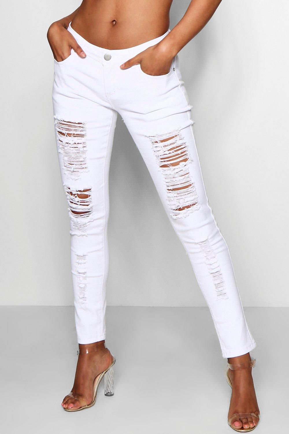 A lady wearing ripped white jeans
