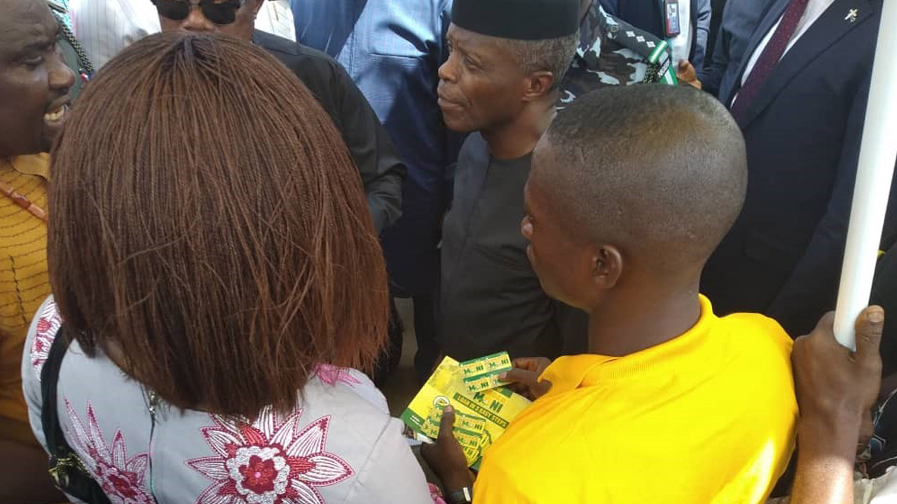 Image: VP, Yemi Osinbajo interacts with a 'One-card Repayment Voucher' Agent in Ochanja Market.