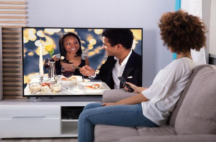 An African American woman watching TV