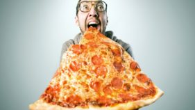 A man holding pizza