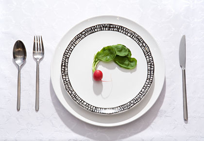 One small radish on a flat plate with a knife, a fork and a spoon